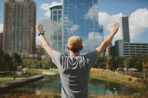 man in a city with his hands raised in worship and praise to God