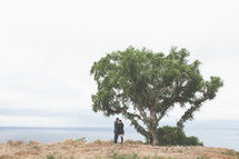 Couple embracing by tree at the ocean.
