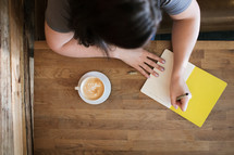a young woman journaling at a coffee shop