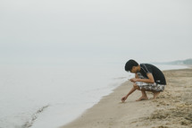 young man playing in the sand on a beach