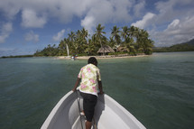 woman on the bow of a boat looking out at tropical water near and island
