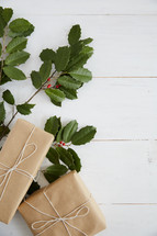 holly and gifts on a white wood background