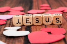 word Jesus in scrabble pieces and a paper heart