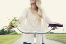 teenage girl riding a bicycle holding a book and flowers.