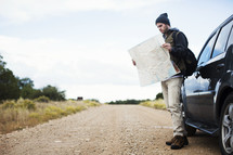 A man standing by his car on a gravel road while studying a road map.