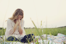 woman sitting on a blanket in the grass praying