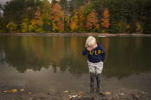 child standing in a pond in rain boots