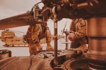soldiers repairing a helicopter