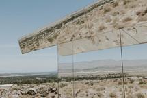 reflection of desert landscape in mirrored glass