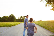 father and son racing on a rural road