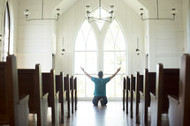 a man kneeling with hands raised in worship at church