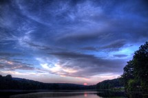 pink and purple clouds over a lake at sunset