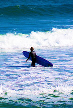 A lone surfer wades out into the ocean to catch a wave in the deep blue sea off the coast of Florida looking for the perfect wave to surf on a sunny day filled with blue skies, calm seas and big waves.