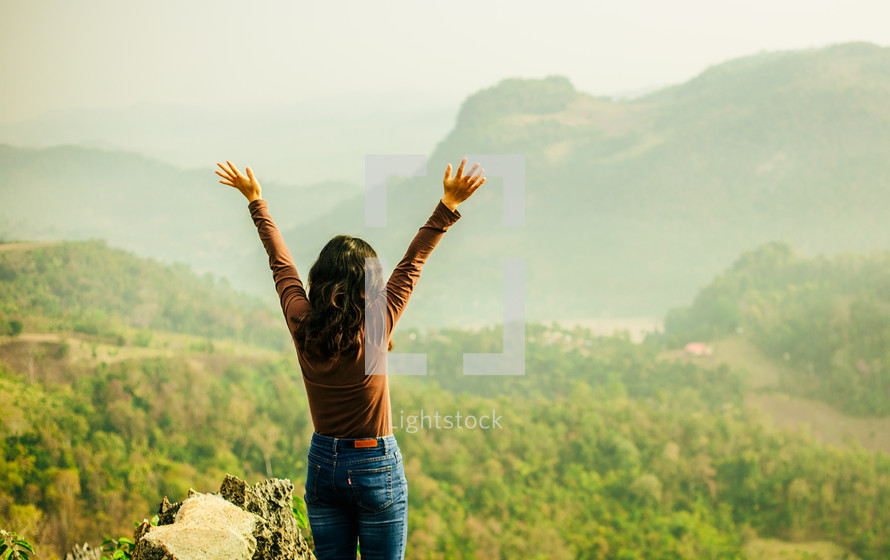 woman standing outdoors with arms raised