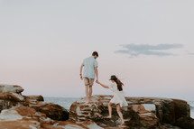 a couple walking on a rocky shore