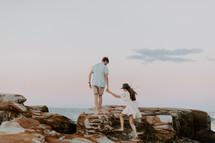 a couple walking on a rocky shore