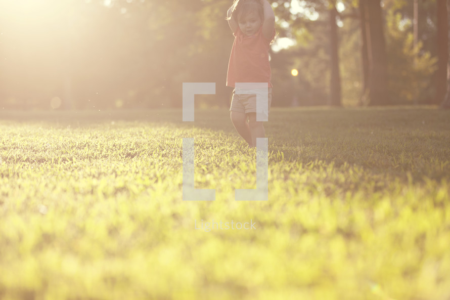 toddler girl walking in the grass at sunset.
