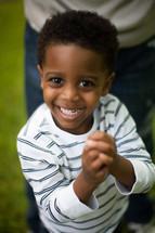 toddler boy smiling with praying hands