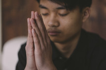 A young man praying with his hands together in front of him.