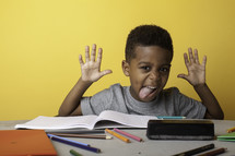 a boy child sticking his tongue out at his desk
