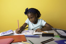 a girl coloring on paper
