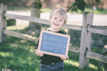 "Boy standing outside holding a ""Happy Mother's Day"" chalk board sign."