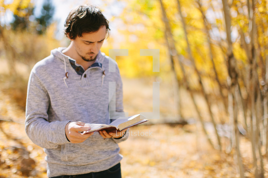Man Reading Bible Outside During Autumn