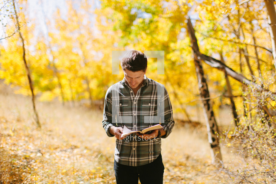 a man standing in a fall forest reading a Bible