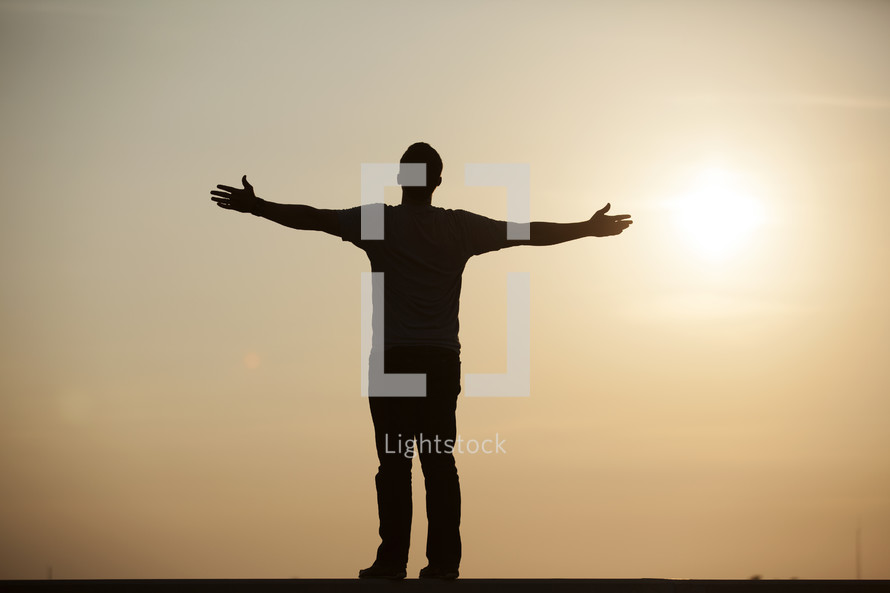 silhouette of a man standing with his arms extended