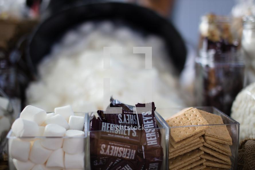 Marshmallows, chocolate bars, and graham crackers -- smores preparation station.