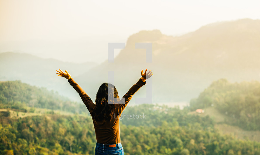 woman standing outdoors with raised hands