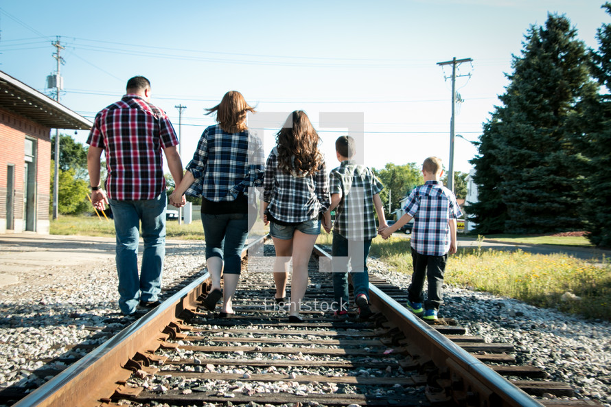 family walking holding hands on railroad tracks