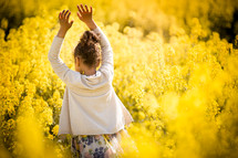 a girl in a field of yellow flowers