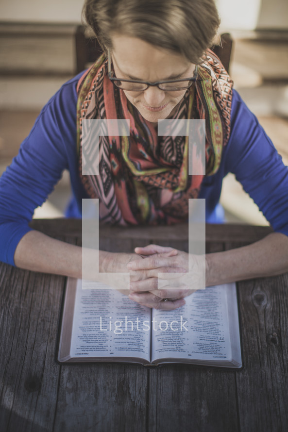 A woman sitting at a table praying with an open Bible