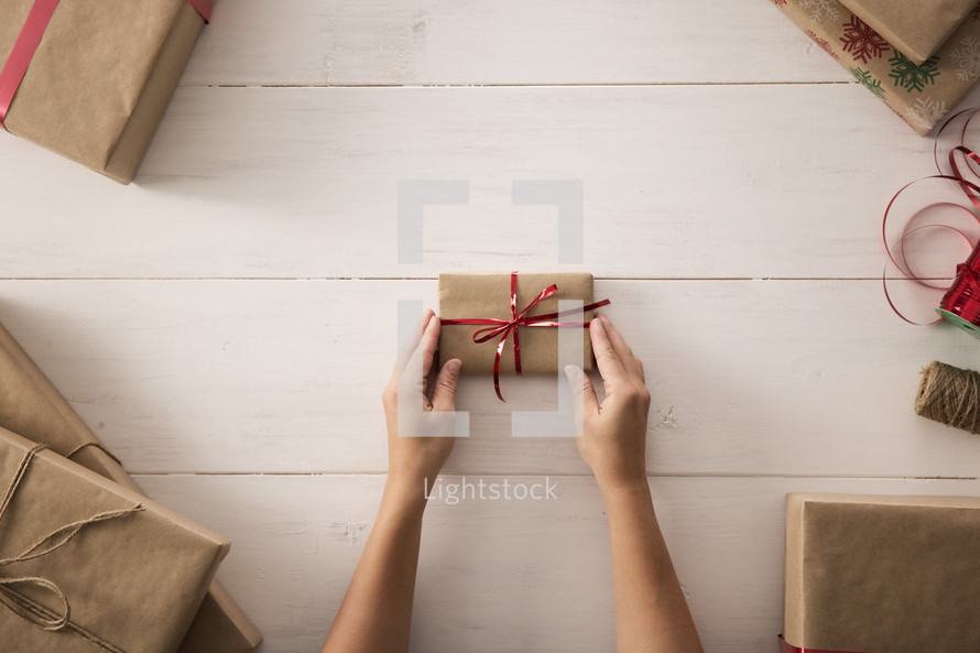 a woman wrapping a Christmas gift with surrounding gifts.