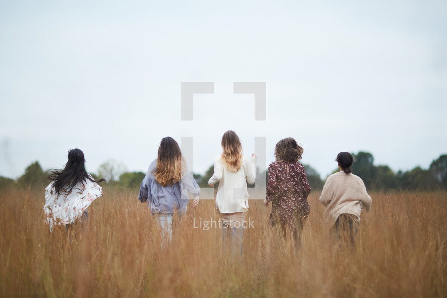 group of women walking through a field