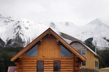 log cabin and snow capped mountain peaks
