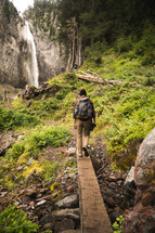 a man hiking in a forest near a waterfall