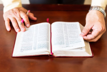 Hands with a pen holding the pages of a Bible on a wooden table.
