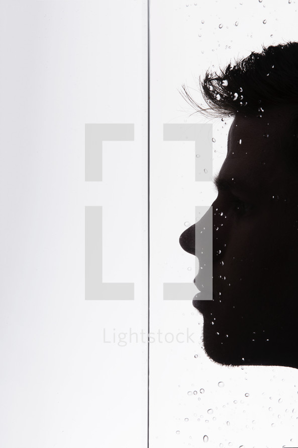 silhouette of a man's face getting wet