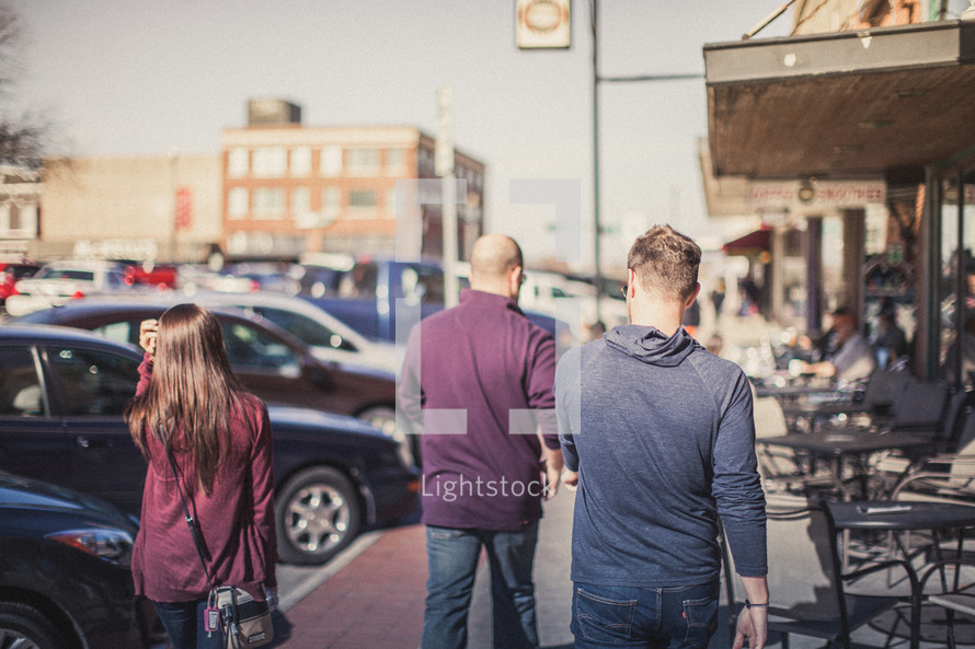 Young people walking down the sidewalk in front of a cafe