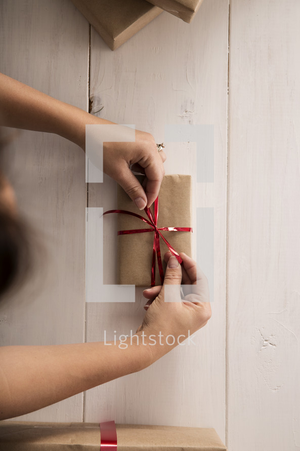 A woman tying a ribbon on a new gift.
