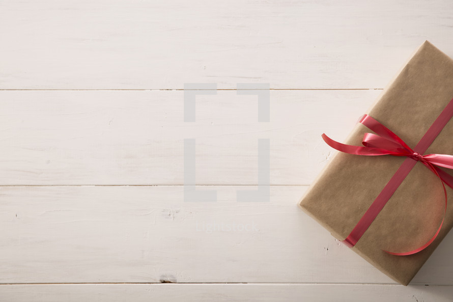 A gift wrapped in brown paper on a white table.