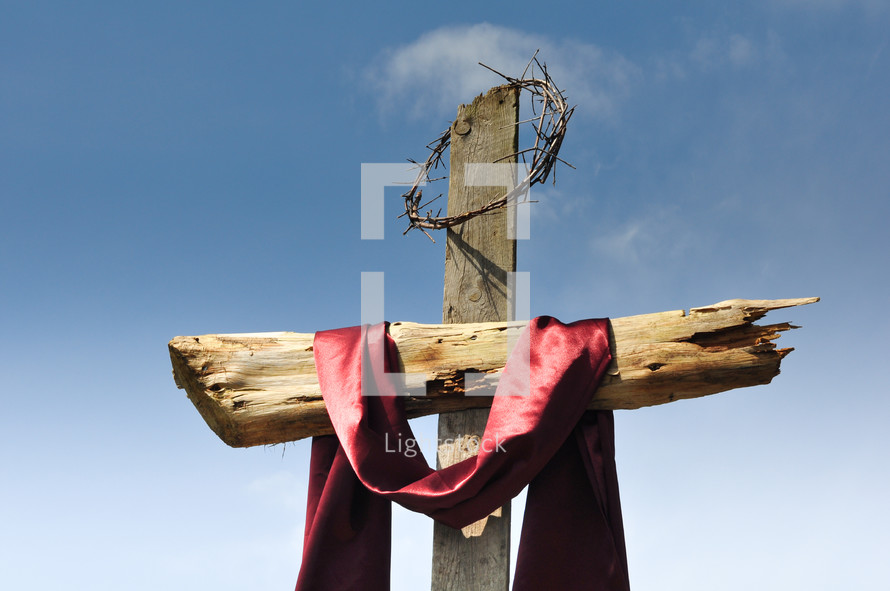 Wooden cross with crown of thorns and red satin fabric against a blue sky.