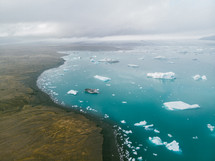 aerial view over icebergs floating in the ocean