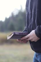 man carrying a Bible outdoors