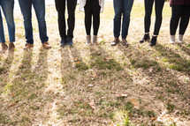 legs of a group standing in grass
