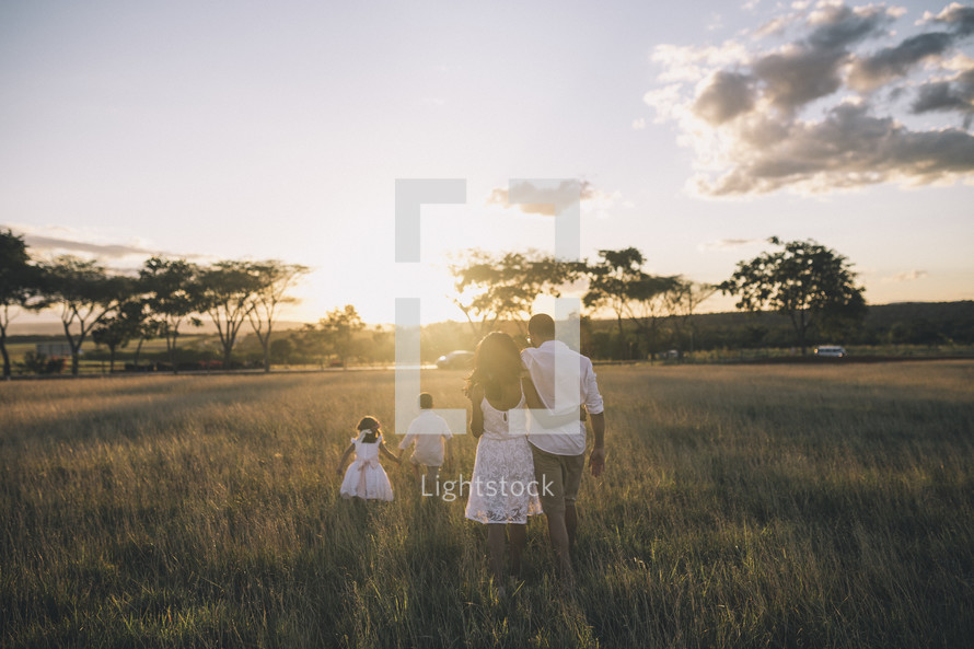 a family walking through tall grass at sunset