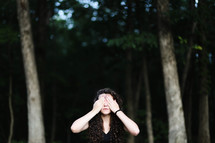 a woman standing in a forest covering her eyes