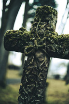 old chiseled stone cross with moss